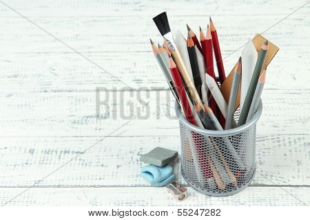 Professional art materials in metal holder, on wooden table