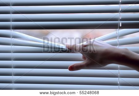 Female hand separating slats of venetian blinds with a finger to see through