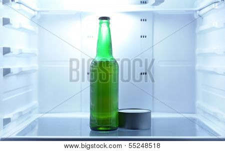 One  beer bottle and canned tune in open empty refrigerator: bachelor fridge concept.