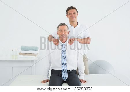 Portrait of a male chiropractor massaging a mature patients shoulder in the office