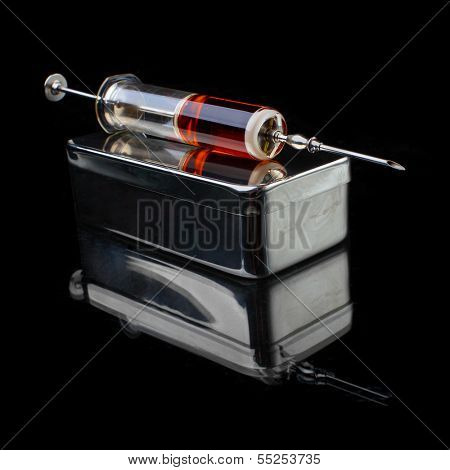 Glass syringe with stainless steel box on a black background.