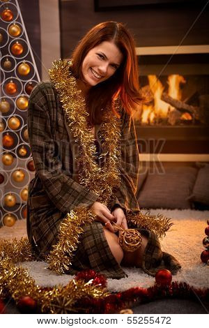 Happy christmas portrait of laughing woman in dressing gown decorating with tinsel and bulb, cosy living room with fireplace.