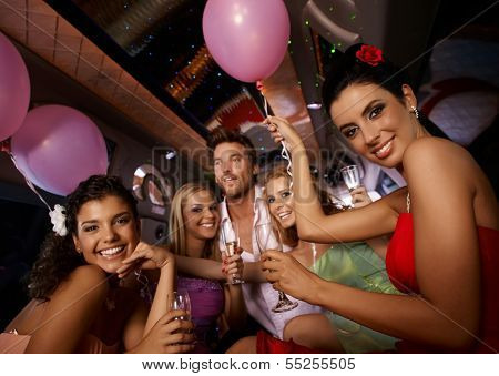 Hen party in limousine with attractive young people.