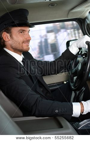 Elegant chauffeur driving luxurious car, smiling.
