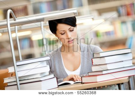 Woman surrounded with piles of books reads sitting at the desk at the library. Information concept