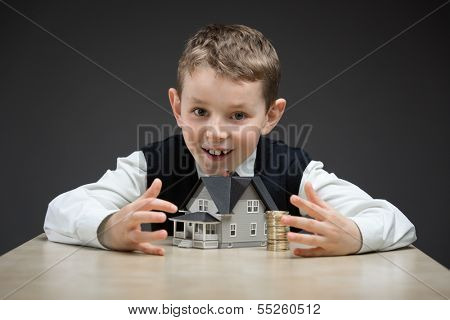 Portrait of little boy taking away house model and pile of coins on grey background. Concept of real estate and purchase