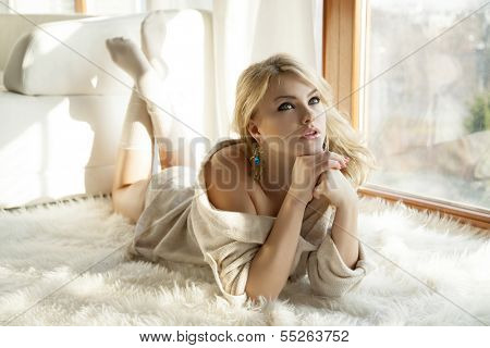 Young slim sexy and attractive blonde woman in brown sweater against the window