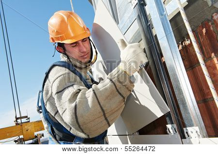 worker builderinstalling big tile on aerated facade constructiona of building