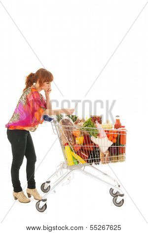 Woman with shopping cart full with dairy grocery products reading list isolated over white background