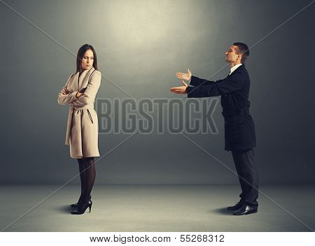 young man apologizing to offended woman
