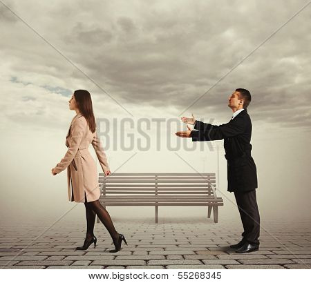 sad man calling outgoing woman in the park