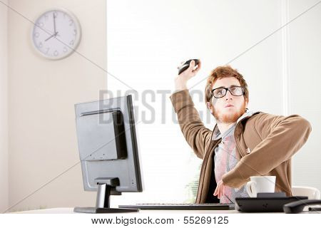 young office worker throwing his mouse away
