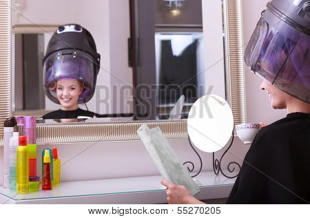 Girl Reading Magazine Drinking Coffee. Hairdryer In Hair Beauty Salon
