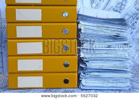 Blue Heap Of Project Drawings In Yellow Folder.