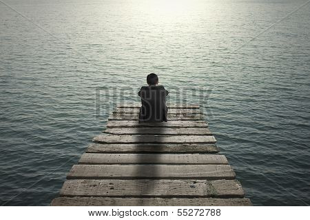 Businessman Sitting And Thinking On Old Wooden Pier To The Sea