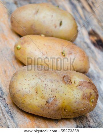 Fresh Potatoes On A Wooden Chopping Board