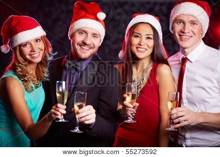 Company of friends in Santa caps holding flutes of champagne in hands