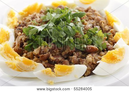 Egyptian foul - or ful - medammes on a plate garneshed with slices of hard-boiled egg and flat-leaf parsley. Foul is probably Egypt's most famous food.
