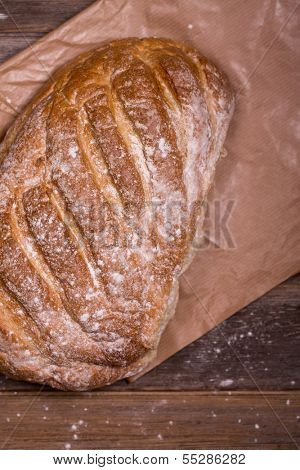 Crusty bloomer loaf, unwrapped from brown paper wrapping, over old wood background