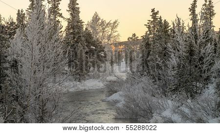 River Flowing Through Winter Landscape
