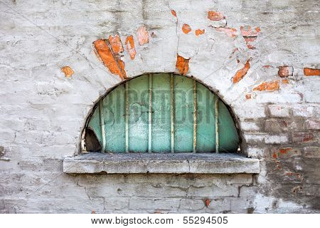 Old semicircular window against the brick-wall