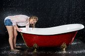 stock photo of bent over  - Wet girl bent over the bathtub under the spray of water - JPG