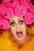 stock photo of drag-queen  - Screaming drag queen with pink foam wig in theater - JPG