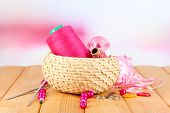 Handicraft supplies in basket on wooden table on bright background