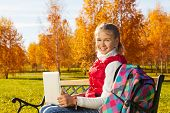 picture of 11 year old  - Happy blond 11 years old girl with amazing smile sitting on the bench with laptop turning back doing homework outside in the autumn park on sunny day - JPG