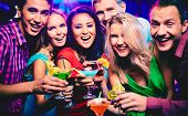 stock photo of cocktail  - Group of happy friends with cocktails toasting at party - JPG