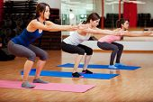 stock photo of outfits  - Three beautiful young women doing some squats and exercising at a gym - JPG
