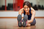 image of stretching exercises  - Pretty young Latin woman doing some stretching exercises and warming up at a gym - JPG