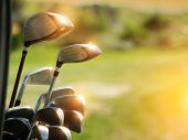 foto of driver  - Golf clubs drivers over green field background - JPG