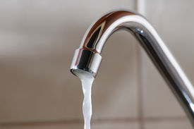 picture of water shortage  - Horizontal image of a tap with water flowing slowly during a period of scarcity - JPG