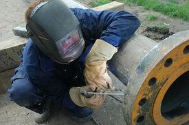 stock photo of pipe-welding  - Welder welding a pipe on a terrain - JPG