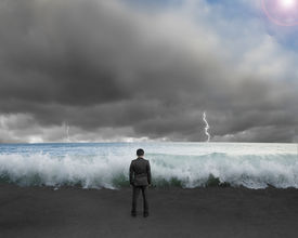 foto of dangerous situation  - Businessman standing toward waves and cludy sky with Lightning thunder to challenge dangerous situation - JPG