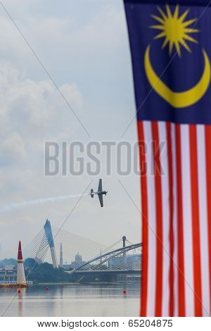 PUTRAJAYA, MALAYSIA - MAY 16, 2014: Yoshihide Muroya of Japan flies over the skies of Putrajaya during the Red Bull Air Race World Championship 2014.  The Malaysian flag is in the foreground.
