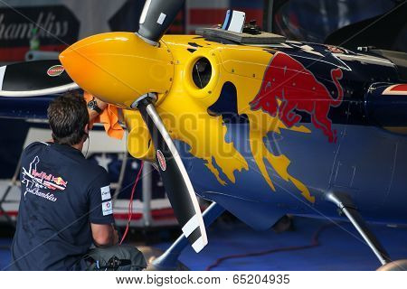 PUTRAJAYA, MALAYSIA - MAY 16, 2014: An unidentified mechanic checks the EDGE 540 V3 aircraft of Kirby Chambliss before flight starts. Kirby Chambliss is taking part in the Red Bull Air Race Putrajaya.