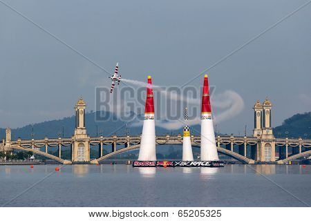 PUTRAJAYA, MALAYSIA - MAY 17, 2014: Paul Bonhomme from Great Britain in an Edge 540 V2 plane flies through the race course over Putrajaya lake at the Red Bull Air Race World Championship 2014.