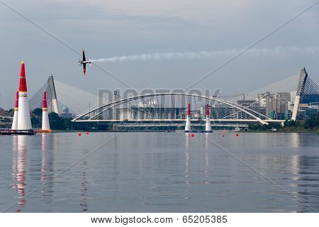 PUTRAJAYA, MALAYSIA - MAY 17, 2014: Nicolas Ivanoff of France in an Edge 540 V2 plane flies across the lake in Putrajaya at the qualifying session of the Red Bull Air Race World Championship 2014.