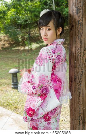 Geisha Leaning Against Wodden Pillar