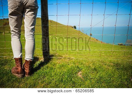 Woman Standing By Fence In Countryside
