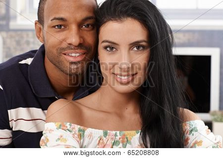 Closeup portrait of beautiful interracial couple smiling at home.