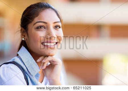 cheerful young indian university girl daydreaming on campus