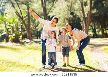 happy young family bird watching in forest