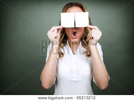 Portrait of young cute girl holding two blank card on her eyes isolated on grey background, surprised facial expression, advertisement concept