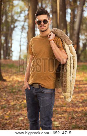 Trendy men holding  jacket over shoulder