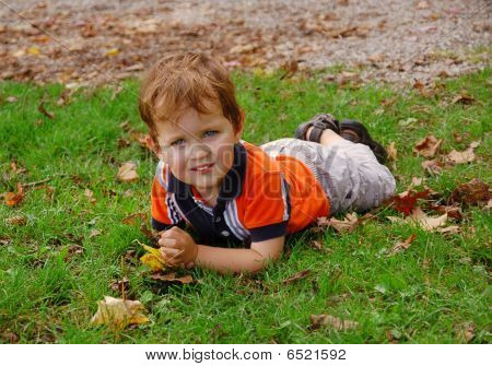 Little boy laying on the grass