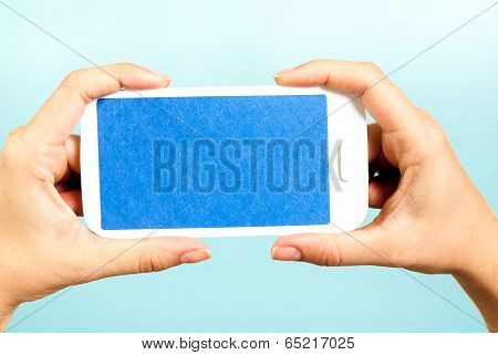Blue screen horizontal smartphone on blue background. Hands holding a cell phone.
