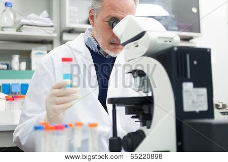 Man using a microscope in a chemical laboratory